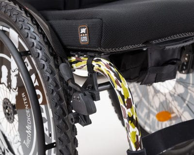 Das Bild zeigt einen Rollstuhl im Wacken-Design fotografiert im Ausschnitt. Die Reifen sind extra breit und die vorderen Stützen im Tarnmuster lackiert