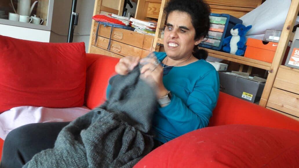 Lydia sitzt auf dem Sofa und strickt