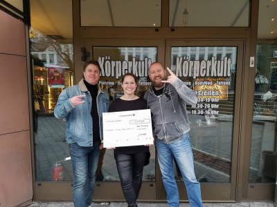 3 Personen von Körperkult überreichen einen Spendenscheck
