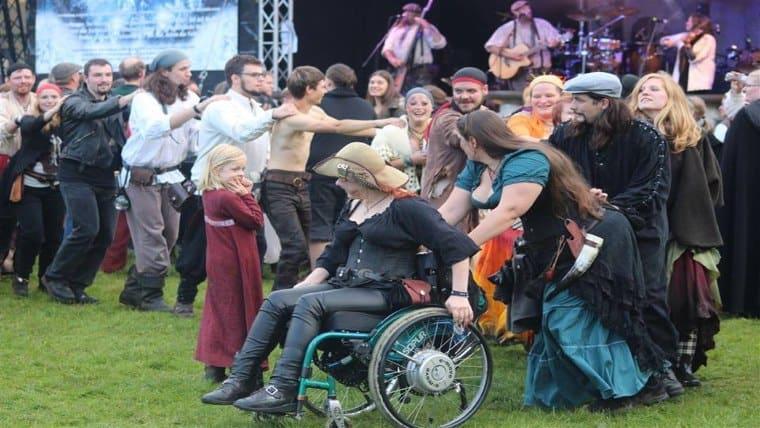Svenja führt eine Truppe von Festival BesucherInnen an. Der Rollstuhl ist dabei Nebensache auf dieser Veranstaltung