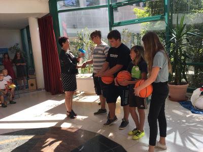 Vier Schülerinnen und Schüler werden von der Direktorin verabschiedet. Es gab sogar noch einen Basketball für die sportbegeisterten Absolventen der Förderschule