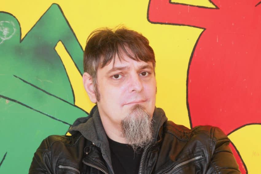 Das Bild zeigt Ron Paustian vor einem mehrfarbigen Hintergrund