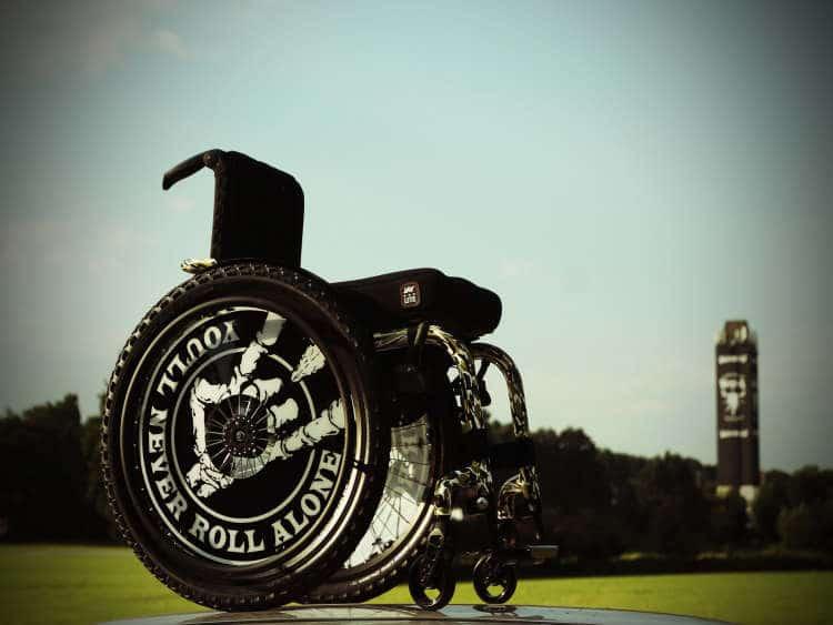 Das Bild zeigt einen Gelände-Rollstuhl in Schwarz. Auf den Radkappen steht You never Roll Alone